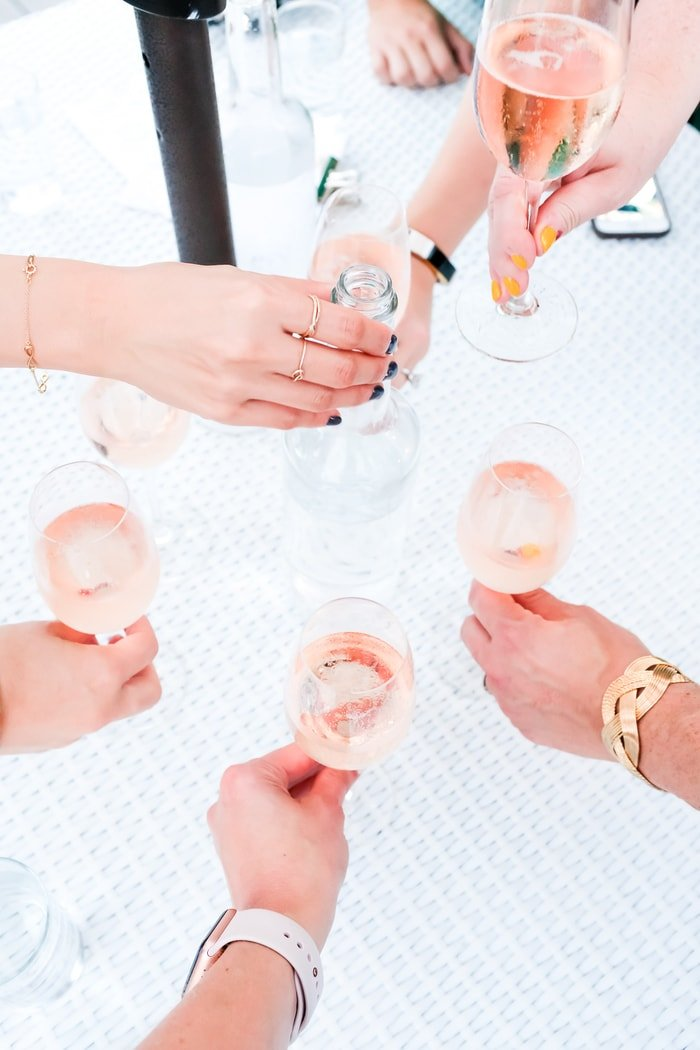 5 woman's hands cheering their pink cocktails.