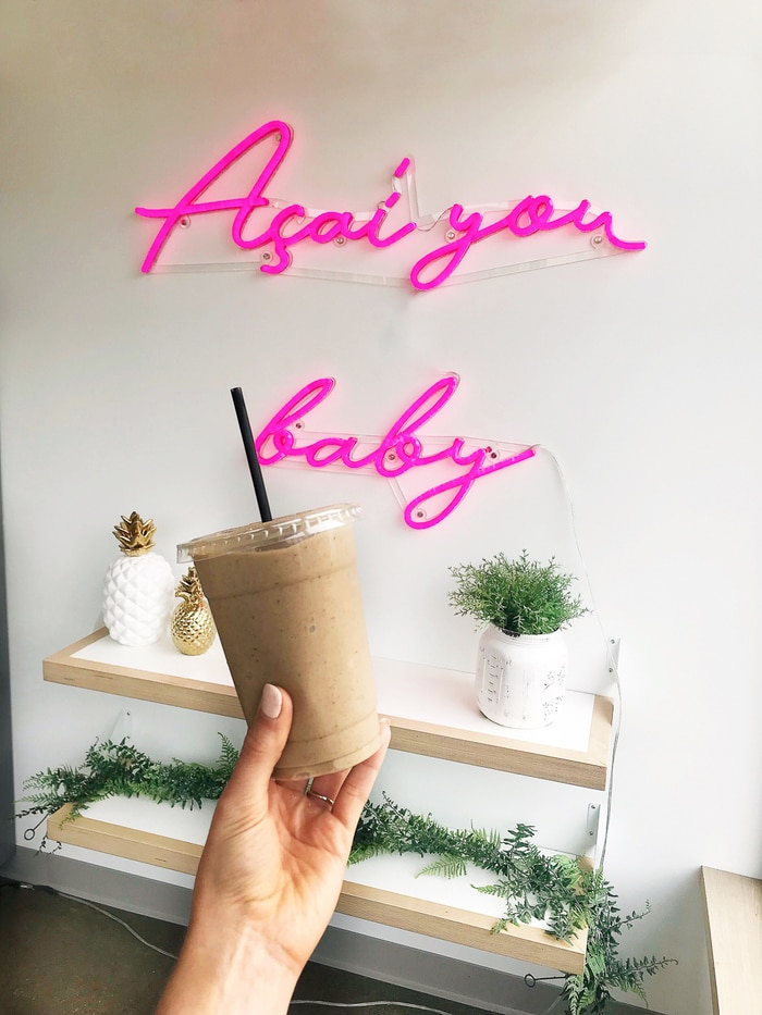 "Woman's hand holding a protein smoothie in front of a wall that has a neon sign that says ""Acai you baby"" and some plants on wall shelves."