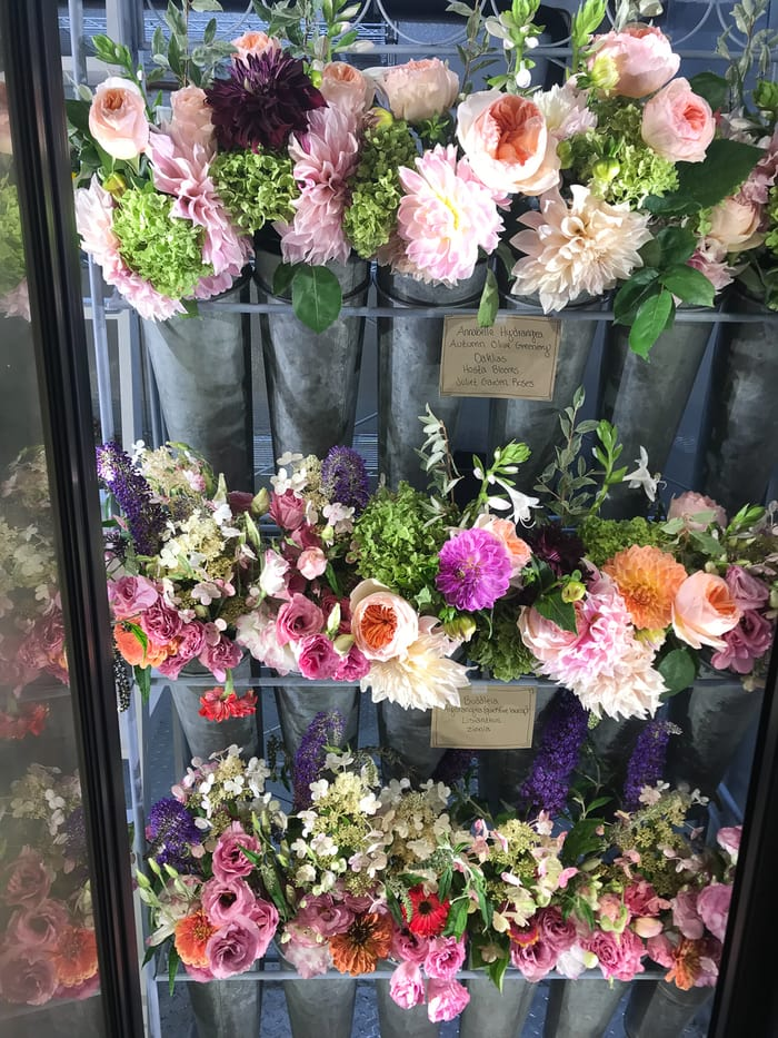 An open cooler filled with flower bouquets.