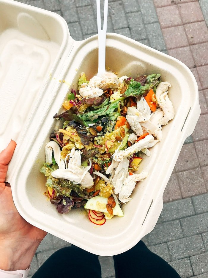 Woman holding a to-go container with a kale chicken Caesar salad.