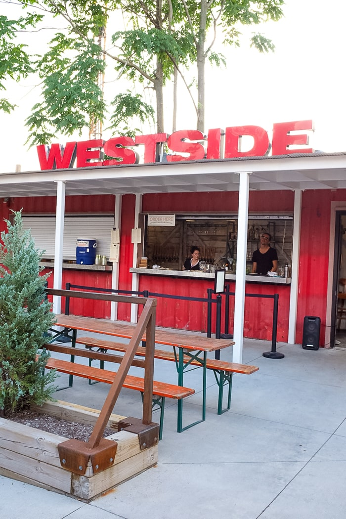 "A restaurant with picnic tables outside and a walk-up ordering window. The sign on the roof says ""Westside""."