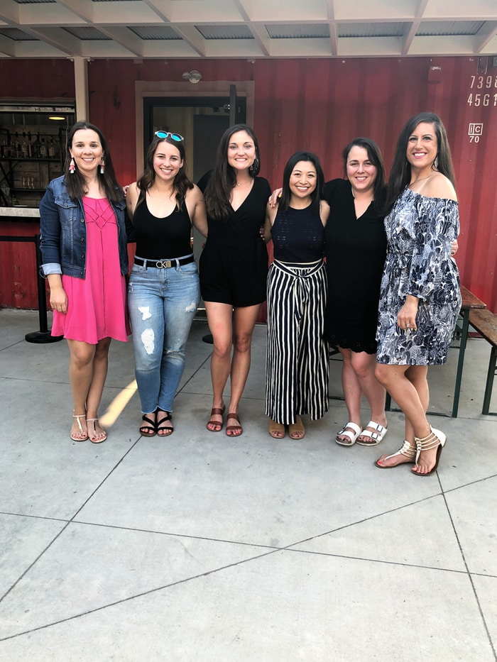 A group of 6 women standing in front of an outdoor restaurant