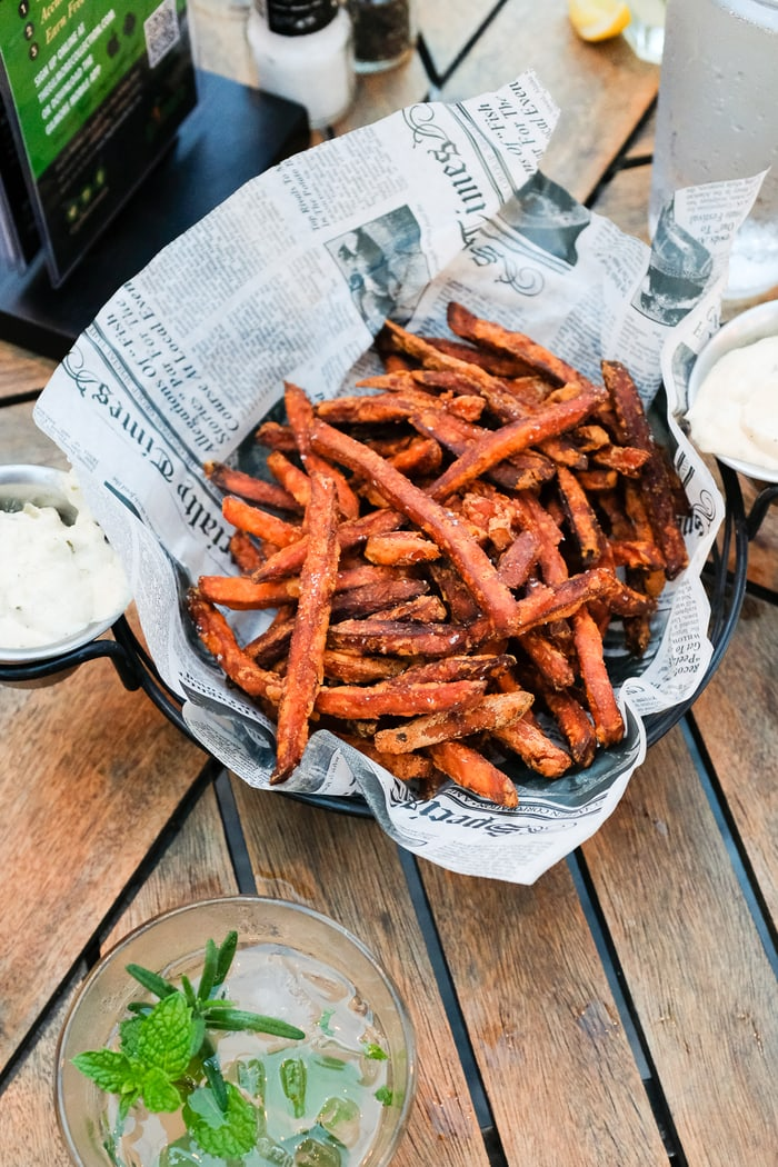 Basket of sweet potato fries in a newspaper lined basket.