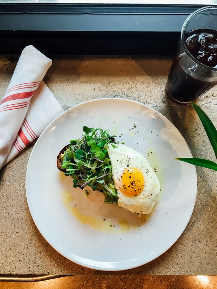 Avocado toast topped with micro greens and a sunny-side-up egg. A glass of iced coffee and a folded cloth napkin are on the side of the plate.