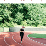 Woman running on a track, wearing a black sports bra and black leggings.