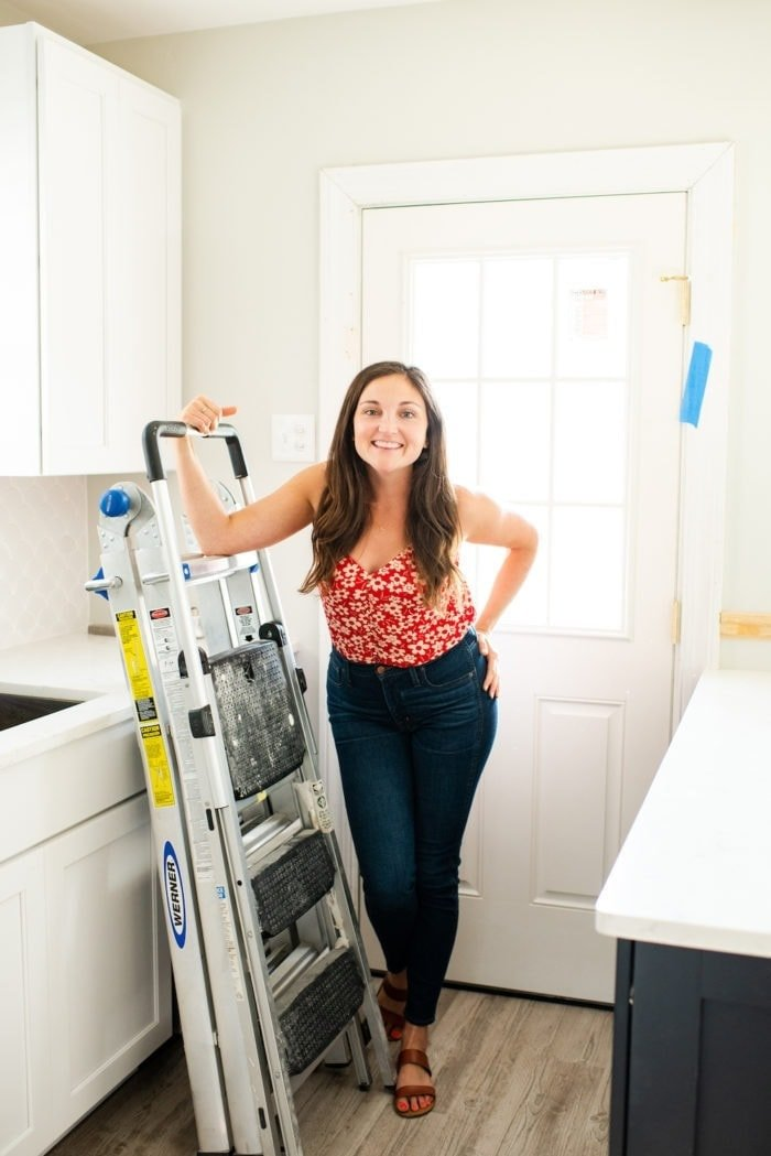 Woman standing in a partially renovated kitchen, leaving on a ladder.