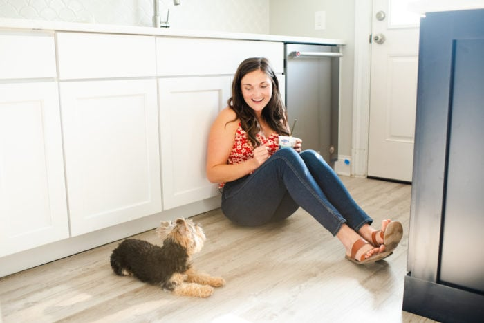 Woman sitting on the floor of her kitchen eating yogurt and laughing while looking at her small dog next to her.