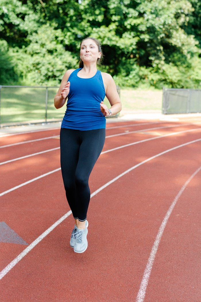 Woman running on track in Athleta Run Free running gear.