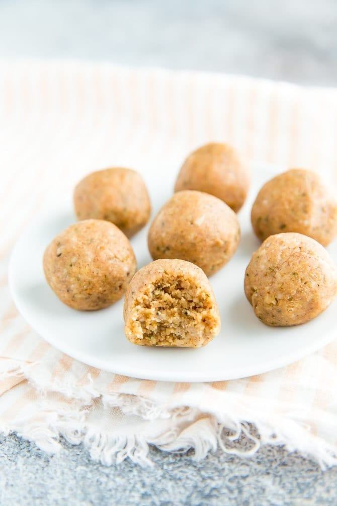Seven coconut protein balls on a white plate with a bite out of one.