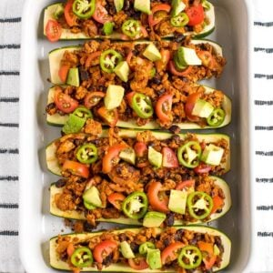 View from above of baking dish filled with turkey taco zucchini boats topped with avocado, jalapeño and tomato. Dish on a kitchen towel.