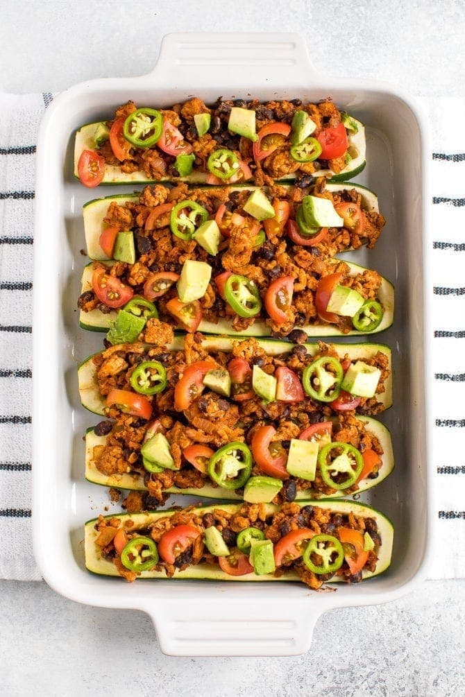 Zucchini boats filled with ground turkey, black beans, tomatoes, and avocado.