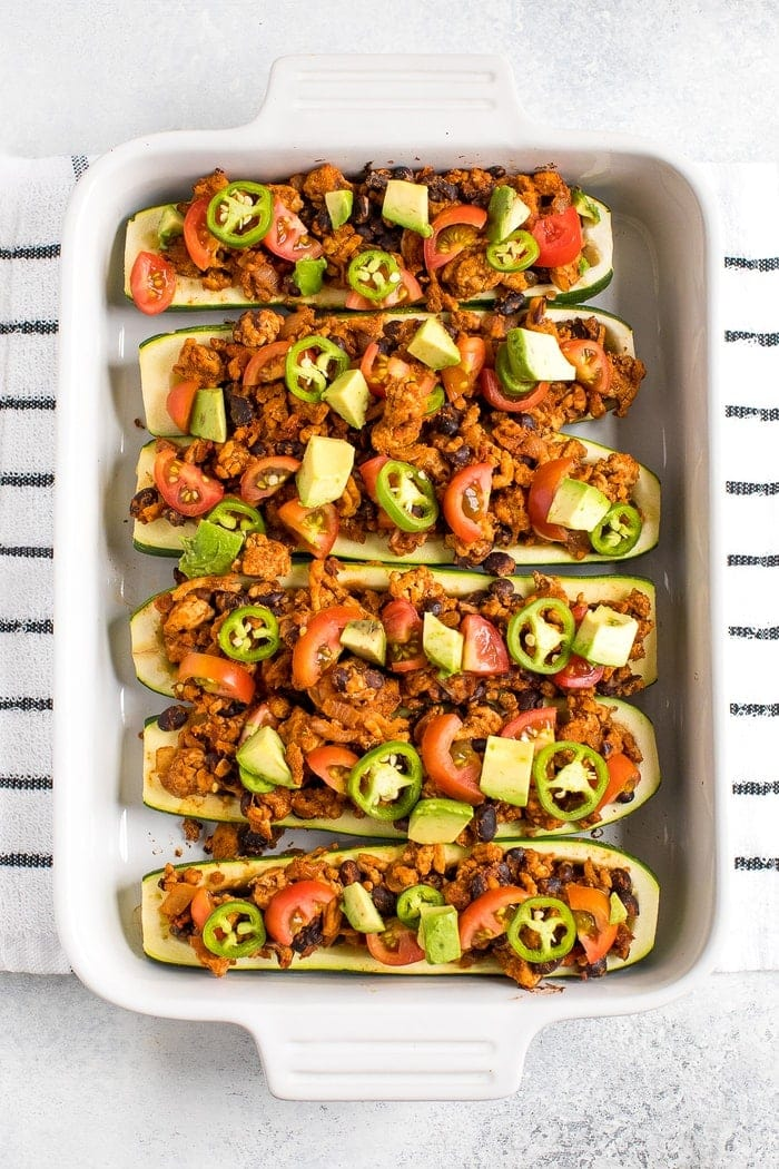 Baking dish filled with turkey taco zucchini boats topped with avocado, jalapeño and tomato. Dish on a kitchen towel.