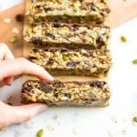 Hand grabbing a slice of tahini fig bars topped with chocolate, slices on a cutting board and surrounded by pumpkin seeds and dried figs.