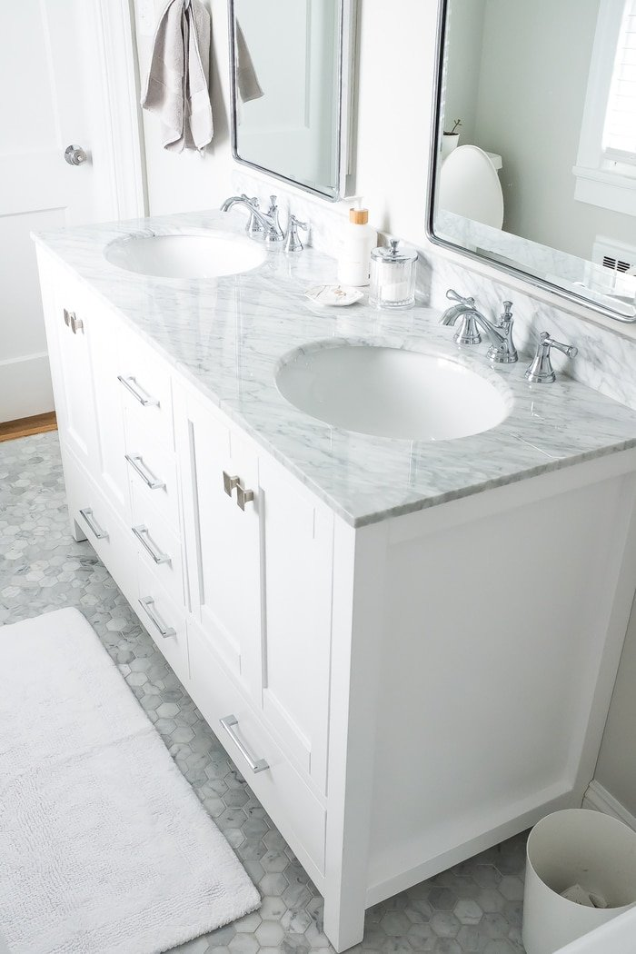 Renovated bright small bathroom with marble floors and white vanity with marble countertop.
