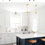 White kitchen with navy island, marble countertops, and wooden stools.