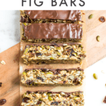 Slices of tahini fig bars on a cutting board, surrounded by oats, pumpkin seeds, and dried fruit.