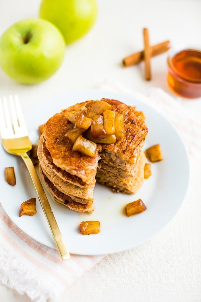 Stack of apple pancakes on a plate with a bite taken out of the stack. The pancakes are topped with cinnamon apples with some extra apple chunks on the plate along with a fork. Maple syrup, apples and cinnamon sticks are in the background.