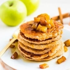 Stack of healthy apple pancakes topped with cinnamon apples. Behind the plate are some Granny Smith apples and cinnamon sticks.