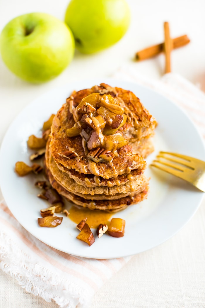Stack of healthy apple pancakes, topped with cinnamon apples and a drizzle of peanut butter. Two apple and two cinnamon sticks are behind the plate.