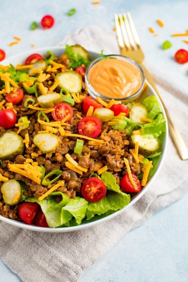 Vegan cheeseburger salad on a plate with fork and neutral napkin.