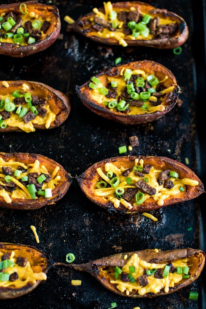 Baked sweet potato skins on a baking stone. The cheese and bacon is melted and crispy. Chives are sprinkled on top.