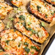 Slices of eggplant on a baking sheet with parchment paper-- they are eggplant pizzas topped with cheese, sauce, and some greens.