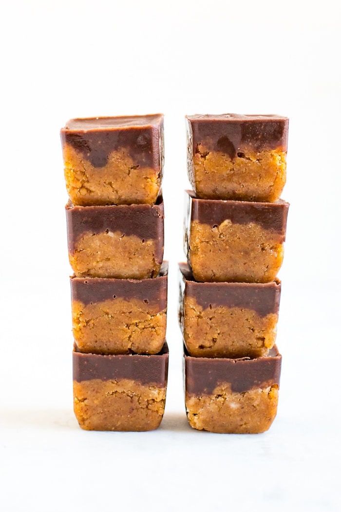 Two stacks of four collagen pumpkin fudge bites. They are cubes of pumpkin fudge topped with a layer of chocolate.