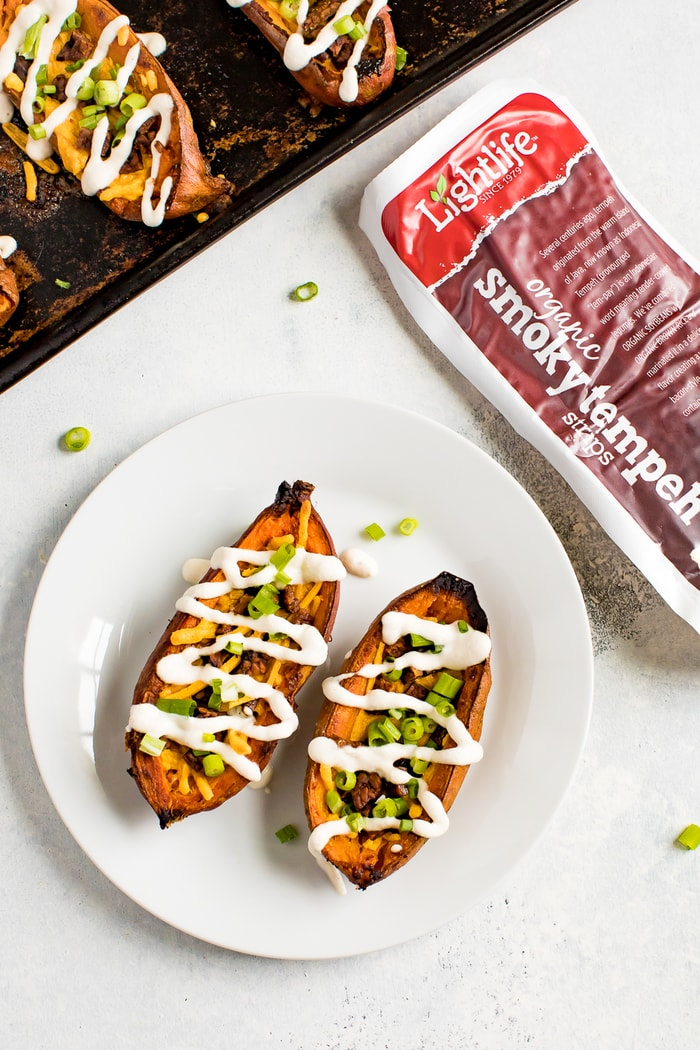 A plate with two sweet potato skins, and a package of tempeh bacon, and the baking stone with the sweet potato skins next to the plate.