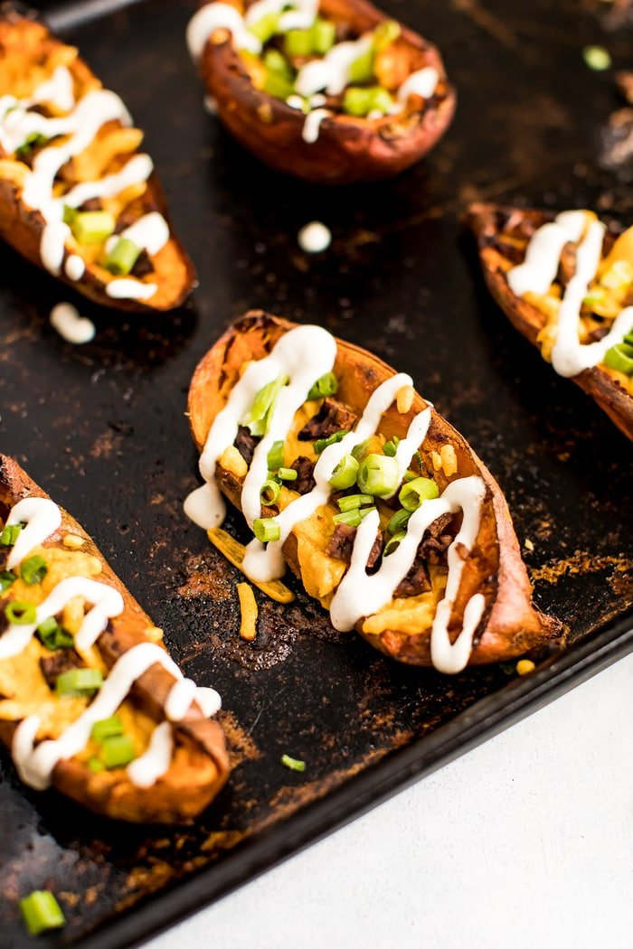 Close up shot of a sweet potato skin on a baking stone. The skins are filled with vegan cheese, bacon, chives, and sour cream drizzle.