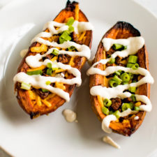 Up close shot of sweet potato skins filled with vegan cheese, vegan bacon, sour cream and chives.