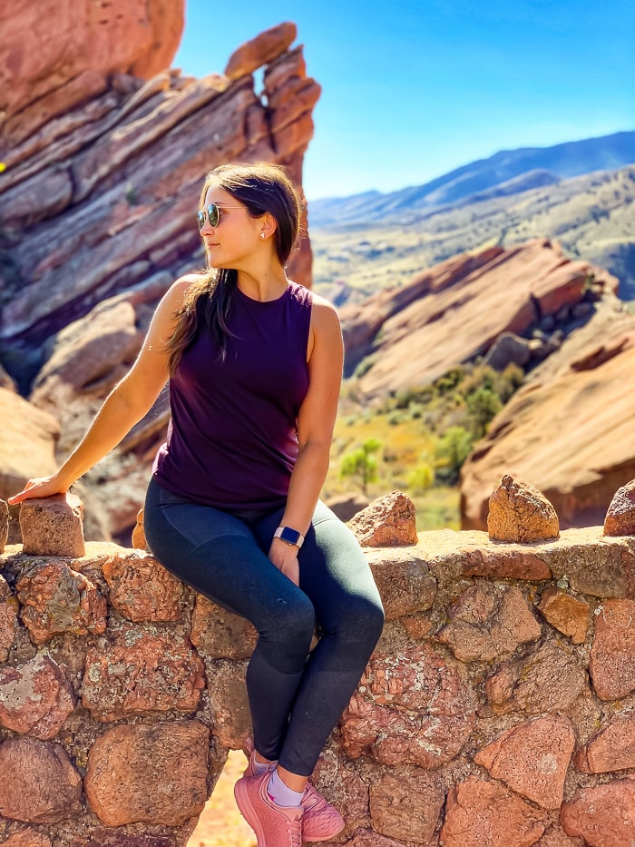 Woman sitting on a ledge and looking out into the distance at Red Rocks in Denver, Colorado.