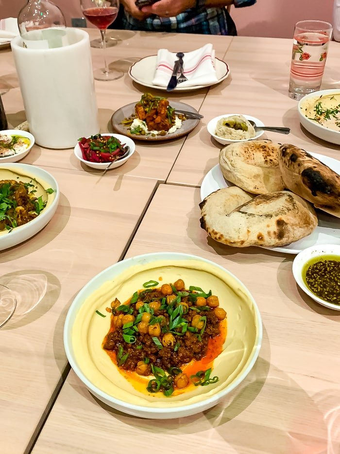 Spread of food at an Israeli restaurant in Denver with plates of chickpea hummus, bread, and drinks.