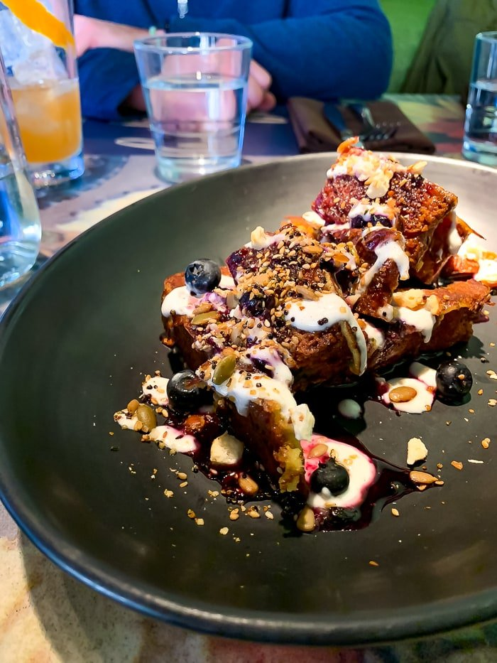 Zucchini bread French toast topped with seeds and berries.