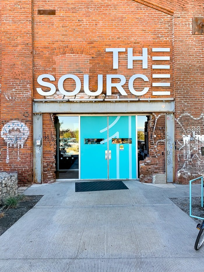 "Outside of a brick building called ""The Source"" with two doors and some graffiti outside."