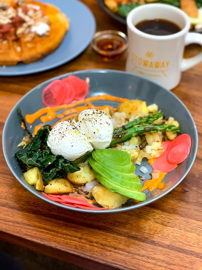 A breakfast bowl with poached eggs, asparagus, greens, avocado, pickled radishes, and potato.