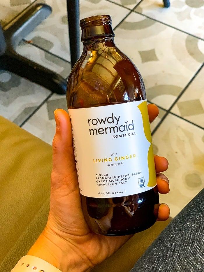 Hand holding a bottle of Rowdy Mermaid ginger kombucha.