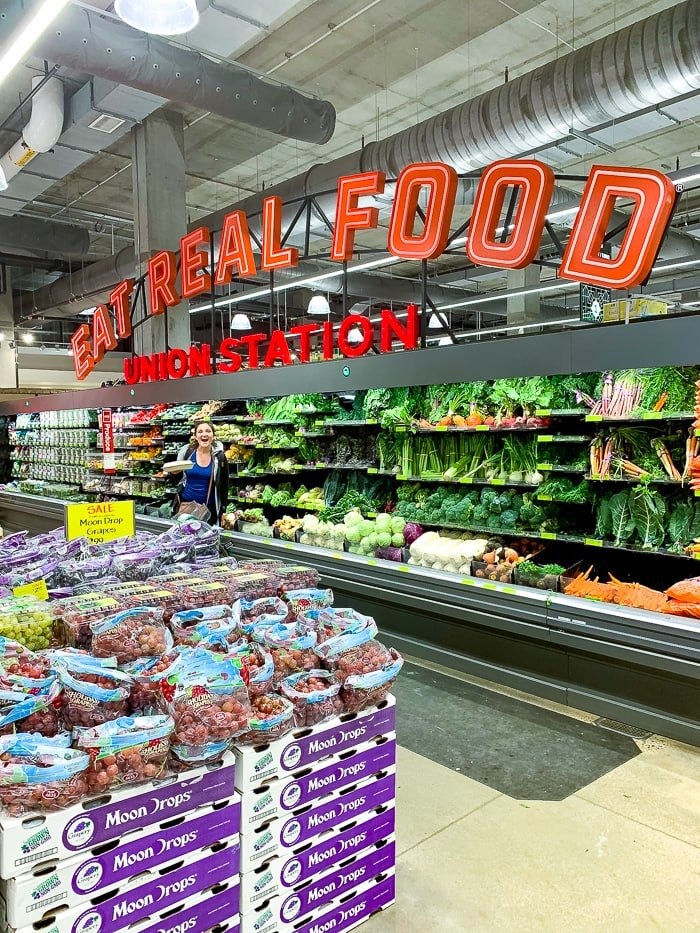 """Woman in front of the produce case of Denver's Union Station's Whole Foods. The sign above says """"Eat Real Food, Union Station""""."""