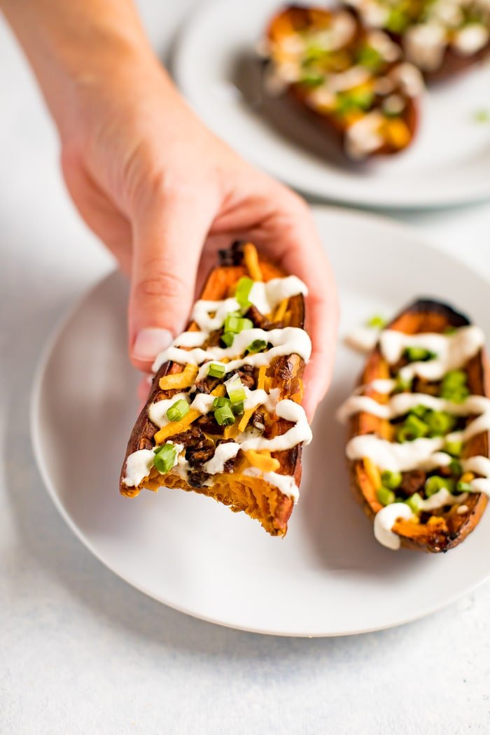 Hand holding a sweet potato skin, filled with vegan cheese, vegan bacon, sour cream and chives. The potato has a bit taken out of it, and there is another sweet potato skin on the plate in the background.