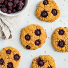 Oatmeal blueberry cookies on a counter next to a bowl of frozen blueberries.
