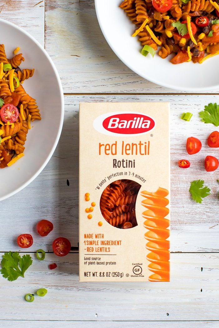 Box of Barilla red lentil rotini on a wood table next to two bowls of enchilada pasta. Tomatoes, peppers and cilantro are sprinkled on the table.