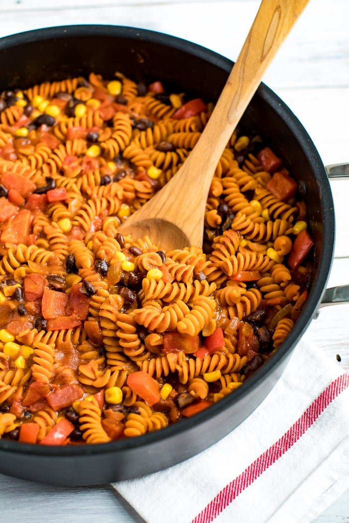Skillet with enchilada pasta, made with red lentil pasta. Pasta is mixed with tomatoes, black beans, and corn. A wood spoon is in the side of the pan.