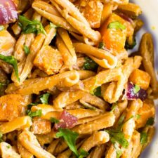 Bowl of roasted butternut squash pasta with tahini sauce.