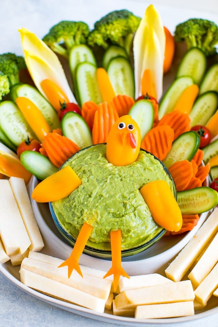 Cute turkey thanksgiving veggies tray. Veggies formed to look like a cute turkey as a veggie tray, with a bowl of guacamole.