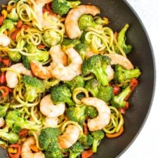 Healthy, broccoli noodle stir fry in a skillet with broccoli, carrots, peppers and teriyaki shrimp.