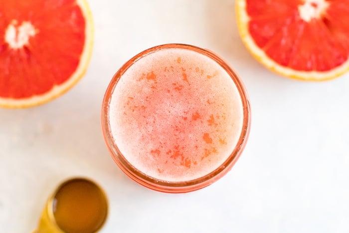 Jar of grapefruit apple vinegar detox drink. Half cut grapefruit and spoon of ACV beside the jar.