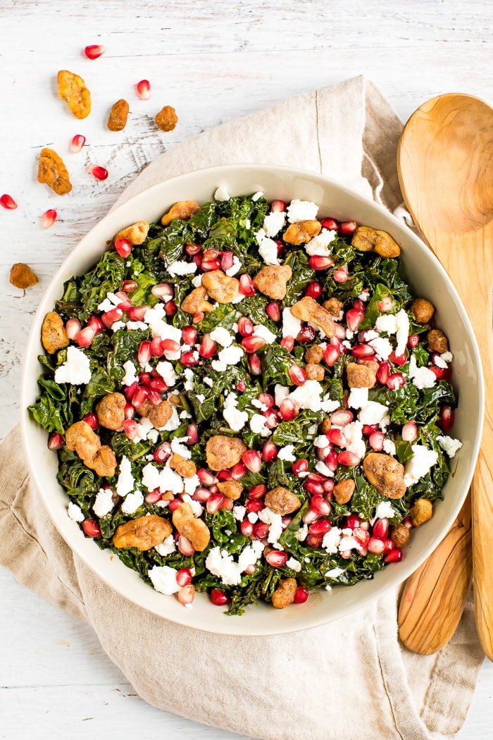 Christmas kale and pomegranate salad with goat cheese topped with candied nuts. Salad is in a serving bowl with wooden serving spoons.