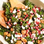 Christmas kale and pomegranate salad with goat cheese topped with candied nuts in a bowl with wooden serving spoons in it.