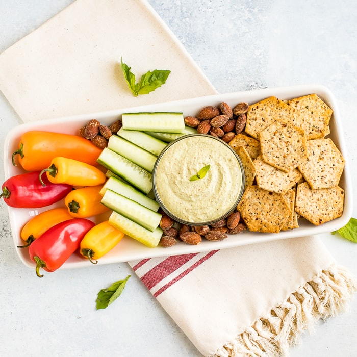 Almond Pesto Dip in a bowl and on a snack tray with cucumbers, almonds, mini peppers, and crackers.