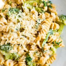 A bowl of creamy, healthy protein packed mac and cheese made with chickpea pasta, broccoli and spinach. Macaroni is topped with extra cheddar.