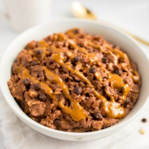 Chocolate peanut butter oatmeal in a bowl topped with a peanut butter drizzle and chocolate chips.